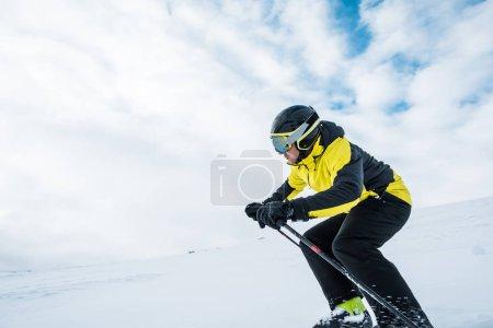 Photo pour Sportif en casque ski sur piste en hiver - image libre de droit