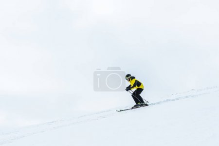 Photo pour Sportsman in helmet holding ski sticks while skiing in wintertime - image libre de droit