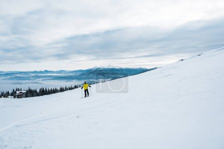 Photo for Skier holding ski sticks while sporting in wintertime - Royalty Free Image