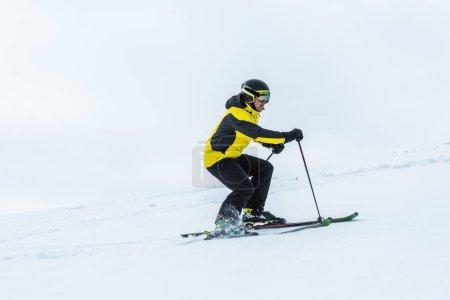 Photo pour Skieur tenant des bâtons de ski et skiant sur les pentes en hiver - image libre de droit