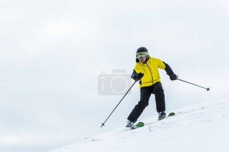 Photo pour Skieur en casque tenant des bâtons et skiant sur la piste en hiver - image libre de droit