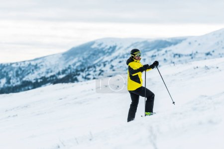 Photo pour Skieur portant un casque tenant des bâtons et se tenant debout sur la pente en hiver - image libre de droit