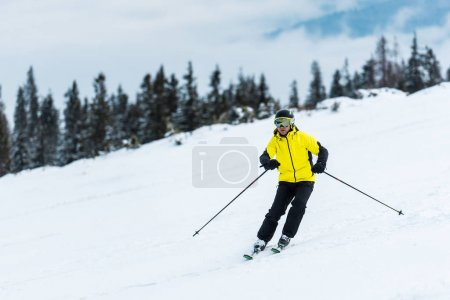 Photo for Skier in helmet holding sticks and skiing on slope in mountains - Royalty Free Image