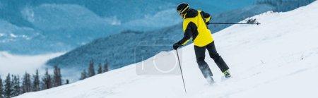 Photo pour Plan panoramique du skieur en casque tenant des bâtons et skiant sur la pente en montagne - image libre de droit