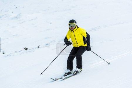 Foto de Esquiador sosteniendo palos y esquiando en la pista con nieve - Imagen libre de derechos