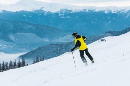 Rückansicht des Skifahrers mit Stöcken und Skifahren am Hang mit Schnee in den Bergen