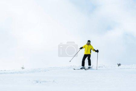 Photo pour Sportif au casque tenant des bâtons et skiant sur la pente avec de la neige en montagne - image libre de droit
