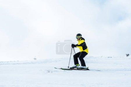 Photo pour Sportif au casque tenant des bâtons et skiant sur piste enneigée - image libre de droit