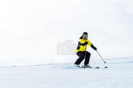 Photo for Sportsman in helmet and goggles holding sticks and skiing on slope with snow - Royalty Free Image