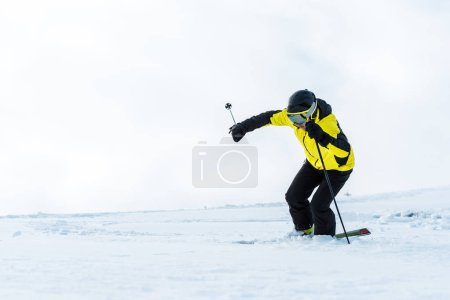 Photo for Sportsman in goggles holding sticks and skiing on slope with snow - Royalty Free Image