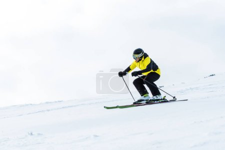 Photo pour Sportsman in helmet and goggles skiing on slope in winter - image libre de droit