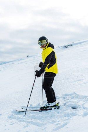 Photo pour Skieur en casque tenant bâtons et debout sur la pente à l'extérieur - image libre de droit