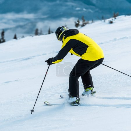 Photo for Skier in helmet skiing on slope near mountains - Royalty Free Image