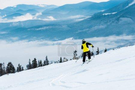 Photo pour Sportif en casque ski sur piste près des montagnes - image libre de droit