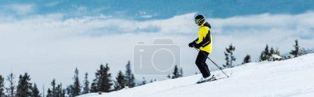 Photo pour Prise de vue panoramique du sportif en casque ski sur piste près des montagnes - image libre de droit