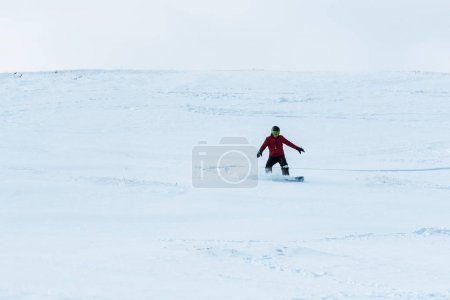 Photo for Snowboarder in helmet riding on slope with white snow outside - Royalty Free Image