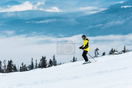 Photo for Skier in helmet holding sticks and skiing on slope in wintertime - Royalty Free Image