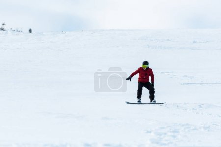 Photo for Snowboarder in helmet and gloves riding on slope with white snow outside - Royalty Free Image