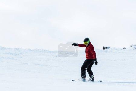 Sportlicher Snowboarder mit Helm und Brille unterwegs auf der Piste