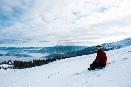 Photo for Snowboarder in helmet sitting on slope against blue sky - Royalty Free Image