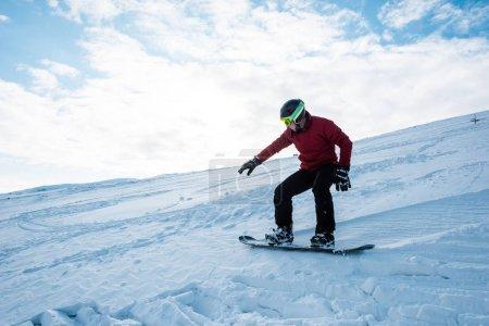 Sportlicher Snowboarder fährt im Winter vor blauem Himmel am Hang