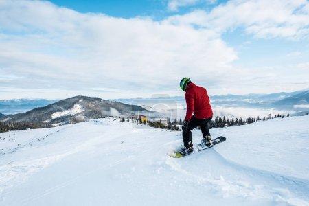 Foto de Snowboarder en casco montando en pendiente en invierno - Imagen libre de derechos