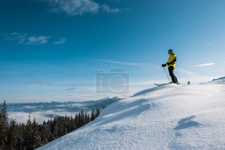 Photo for Skier holding ski sticks and standing against blue sky in mountains - Royalty Free Image