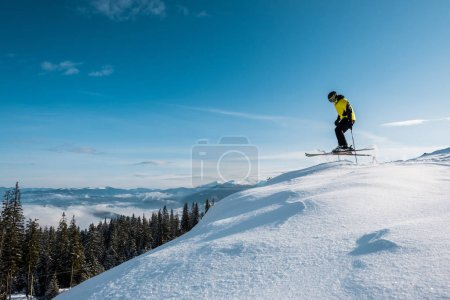 Photo for Side view of skier holding ski sticks and jumping against blue sky in mountains - Royalty Free Image