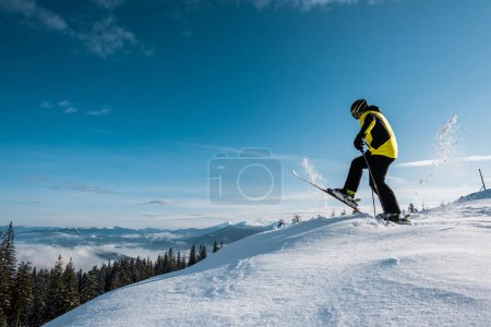 Photo for Side view of skier holding ski sticks and making step against sky in mountains - Royalty Free Image