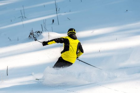 Photo for Back view of sportsman in helmet holding ski sticks while skiing on snow - Royalty Free Image