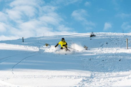 Photo pour Sportsman in helmet holding ski sticks while skiing on slope outside - image libre de droit