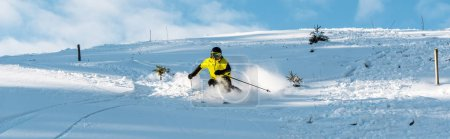 Photo for Panoramic shot of skier in helmet holding ski sticks while skiing on slope outside - Royalty Free Image
