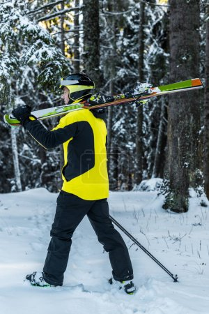 Photo pour Sportsman in goggles holding ski sticks and skis while walking near firs - image libre de droit
