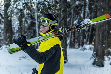 Photo pour Skieur en lunettes tenant des bâtons de ski et des skis près des sapins - image libre de droit