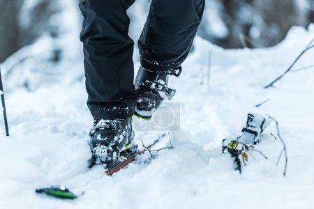 Foto de Vista panorámica del esquiador al caminar por la nieve cerca de los esquís en invierno. - Imagen libre de derechos