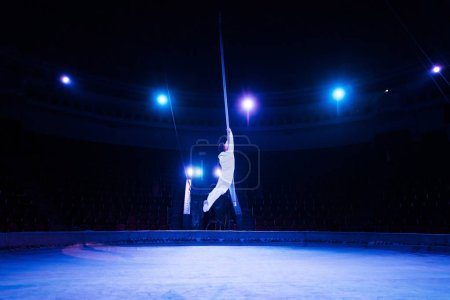 Photo for Blue light near acrobat performing in arena of circus - Royalty Free Image