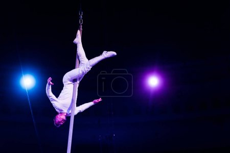 Photo for Acrobat balancing on metallic pole in arena of circus - Royalty Free Image