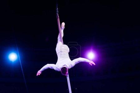 Photo pour Acrobate performant à l'envers sur pôle métallique dans l'arène du cirque - image libre de droit
