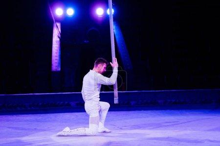 Photo pour Vue latérale de l'acrobate debout sur le genou près du pôle métallique - image libre de droit