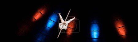 panoramic shot of acrobat balancing on pole in arena of circus