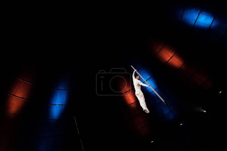 low angle view of athletic acrobat balancing on metallic pole in arena of circus