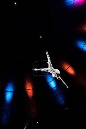Photo pour Vue à faible angle de l'acrobate athlétique équilibrage sur pôle métallique dans l'arène du cirque - image libre de droit