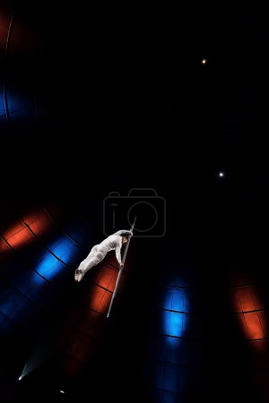 Photo for Low angle view of athletic man balancing on metallic pole near lighting  in arena - Royalty Free Image