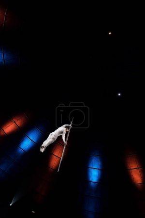 Photo pour Vue à faible angle de l'homme athlétique équilibrage sur pôle métallique près de l'éclairage dans l'arène - image libre de droit