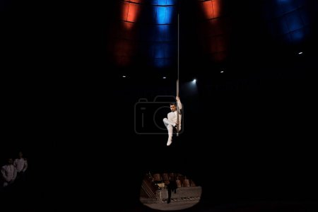 Photo for Spotlights on acrobat performing acrobatic exercise on metallic pole in circus - Royalty Free Image