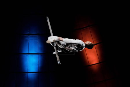athletic acrobat balancing on metallic pole near blue and red lighting in circus