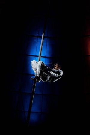 Photo pour Acrobate beau et fort performant sur pôle métallique lumière bleue soignée - image libre de droit