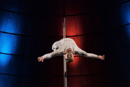 Photo for Strong acrobat with outstretched hands looking at camera while performing on metallic pole - Royalty Free Image