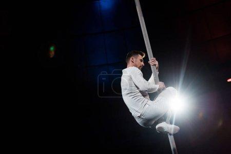 Photo pour Contre-jour près d'acrobate fort performant sur pôle métallique - image libre de droit