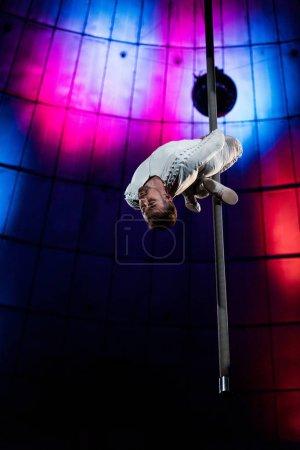 Photo pour Acrobate fort avec les yeux fermés performant sur le pôle métallique - image libre de droit